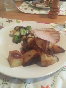 dinner of roast pork, potatoes and brussel sprouts
